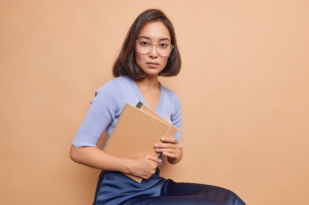 Horizontal shot of asian schoolgirl carries spiral notebooks