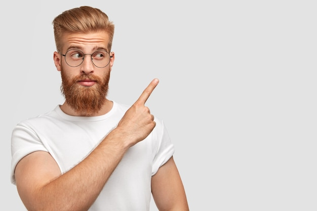 Horizontal shot of attractive caucasian male has ginger hair and beard, points with fore finger aside, dressed in t-shirt in one colour with wall