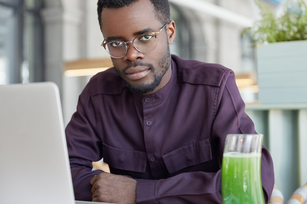 Horizontal shot of attractive dark skinned male manager does work on portable laptop computer, has thoughtful focused serious
