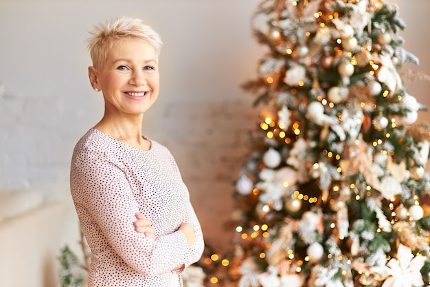 Horizontal shot of attractive elegant short haired mature woman in festive mood celebrating christmas posing at tree decorated with toys and garland, keeping arms crossed on her chest, smiling