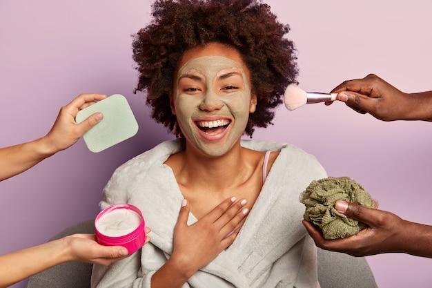 Inquadratura orizzontale del modello femminile attraente che ride sinceramente, tiene la mano sul petto, applica una maschera all'argilla facciale per il ringiovanimento della pelle, riceve trattamenti di bellezza