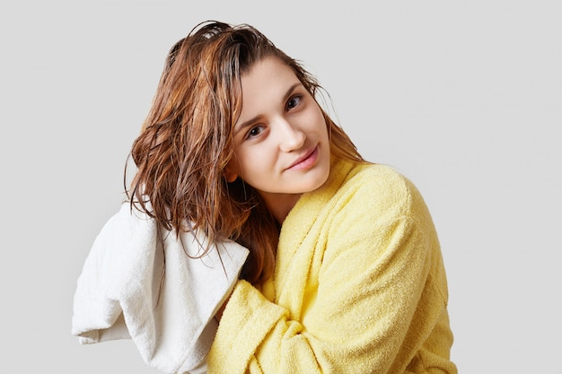 Horizontal shot of attractive female wipes wet hair with towel