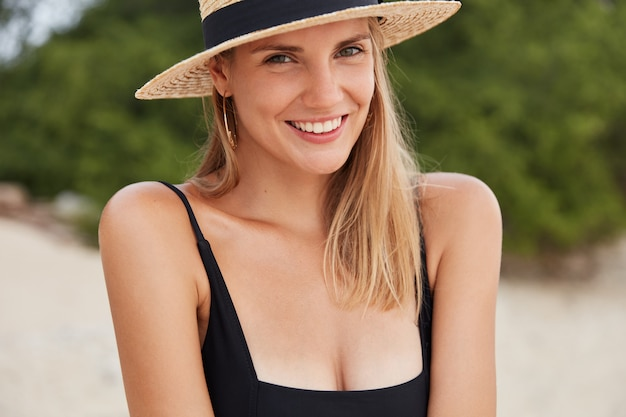 Horizontal shot of attractive female with shining smile spends summer resort on beach, wears black bikini and straw hat, has positive expression, bathes in sun. people and recreation concept