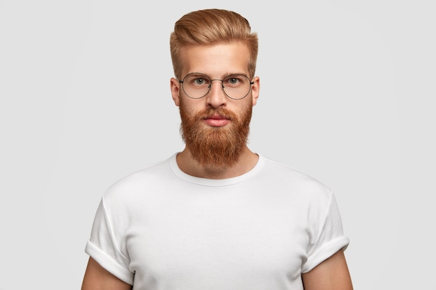 Horizontal shot of attractive hipster looks seriously directly at camera