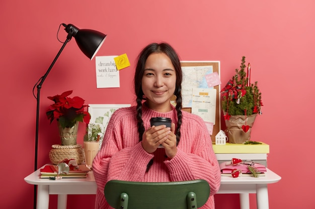 Horizontal shot of attractive korean girl holds takeaway coffee, sits at chair near her workplace, finishes working, stickers on pink wall.