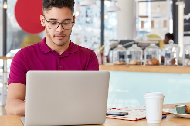 Horizontal shot of attractive man in spectacles, watches video on his laptop, writes on keyboard, models in cafeteria, drinks take out coffee, prepares for business conversation. networking concept