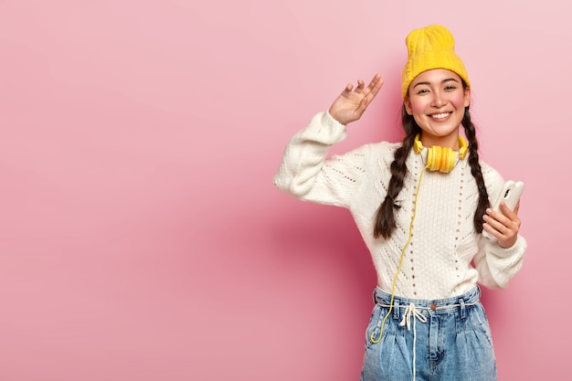 Horizontal shot of attractive mixed race woman holds modern cellphone, dances and wears headphones around neck, poses against pink background, copy space