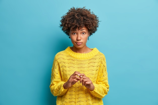 Horizontal shot of attractive serious woman with curly hair keeps hands together and looks curiously at camera listens attentively interlocutor dressed in casual jumper isolated on blue wall