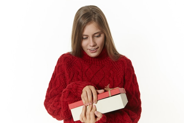 Horizontal shot of attractive stylish young lady wearing maroon knitted pullover holding box, opening it, being excited, receiving present on her birthday. pretty girl posing with paper box