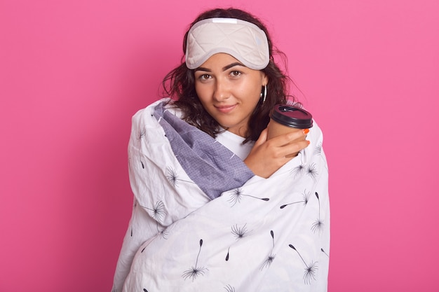 Horizontal shot of attractive woman holding responsable coffee cup