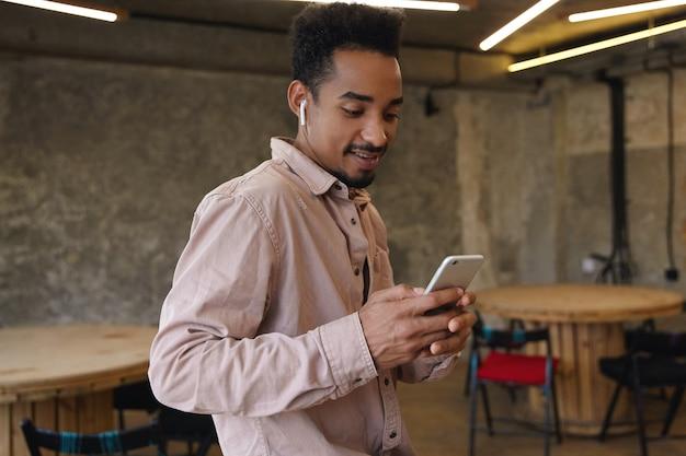 Colpo orizzontale di attraente giovane maschio dalla pelle scura con la barba che tiene il telefono cellulare e controlla i social network mentre si aspetta gli amici nella caffetteria della città, indossando abiti casual e auricolari