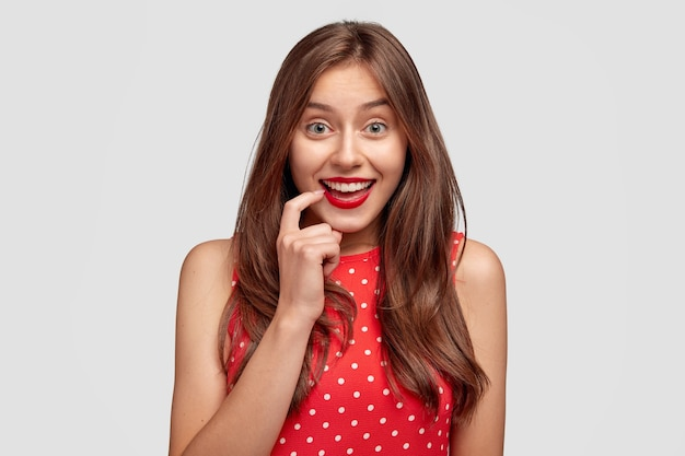 Horizontal shot of attractive young european female wears red lipstick, has joyful expression, smiles broadly, dressed in summer red polka dot dress