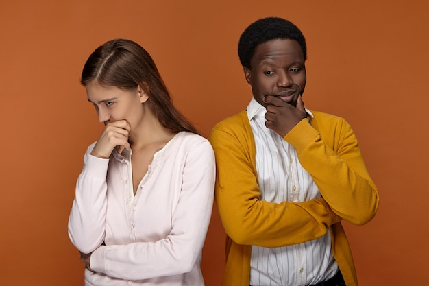 Horizontal shot of attractive young european woman and handsome afro american man in neat casual clothes having pensive thoughtful facial expressions, touching faces, being deep in thoughts