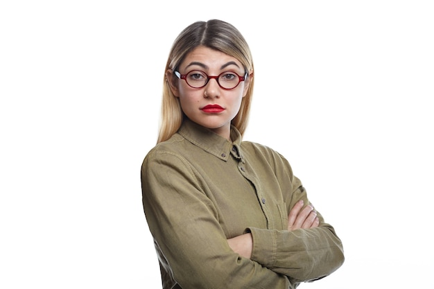 Horizontal shot of attractive young female with blonde loose hair and red lips keeping arms folded, her look and posture expressing dislike or disagreement about some business decision or idea