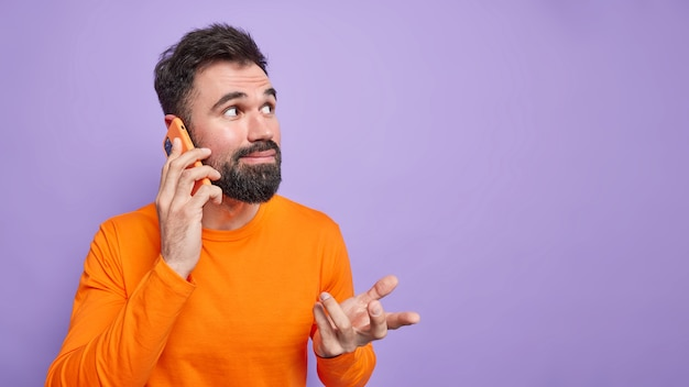 Horizontal shot of bearded confused man raises hand has puzzled expression, talking by phone