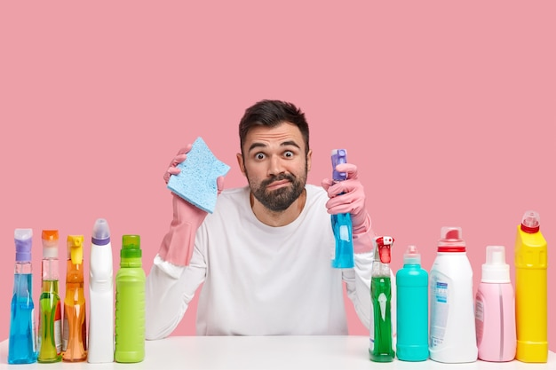 Horizontal shot of bearded guy from cleaning service holds sponge and washing spray, cleans kitchen furniture with rag, uses different solvents