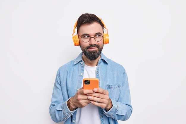 Horizontal shot of bearded satisfied bearded man chooses music from playlist looks away holds smartphone and headphones dressed in denim shirt