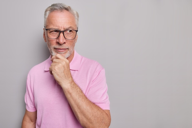 Horizontal shot of bearded thoughtful man holds chin looks pensively