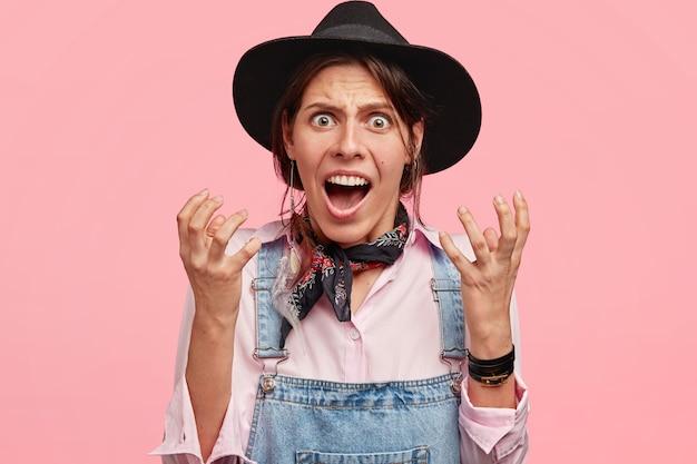 Colpo orizzontale di bei gesti del lavoratore agricolo femminile infastidito, ha un'espressione facciale irritata, dispiaciuto del lavoro, indossa un cappello nero e una salopette di jeans isolata sopra il muro rosa
