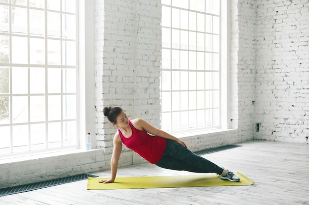 Horizontal shot of beautiful brunette young female with fit athletic body performing one handed side plank pose on fitness mat in gym. sporty girl doing vasisthasana while practicing yoga indoors