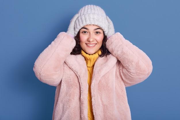 Horizontal shot of beautiful cheerful female wearing faux fur coat