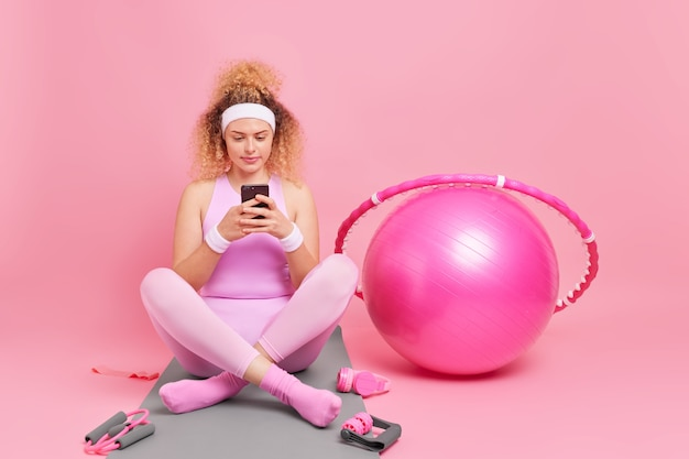 Horizontal shot of beautiful curly female model in good shape sits crossed legs on fitness mat uses mobile phone checks burned calories in special app uses sport equipment