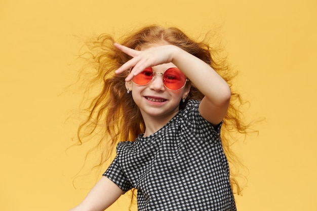 Horizontal shot of beautiful happy trendy little girl with curly ginger hair enjoying dancing,  with cheerful broad smile, wearing sunglasses. music, dance, fun and children concept