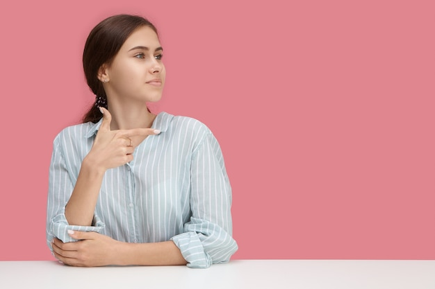 Horizontal shot of beautiful joyful young in stylish striped blue shirt working at office desk and making gesture, pointing index finger at blank pink wall with copyspace for your promotional content