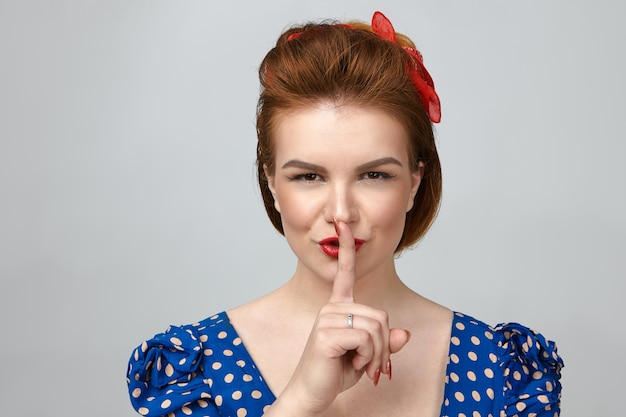 Horizontal shot of beautiful pin up girl in vintage clothes saying shush, holding index finger at her lips and smiling mysteriously, asking for silence, making suprise party for her husband