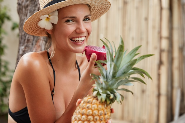 Horizontal shot of beautiful smiling woman with broad shining smile, wears summer hat and bathing suit, holds tropical fruits, enjoys unforgettable summer rest, spends leisure time in tropics