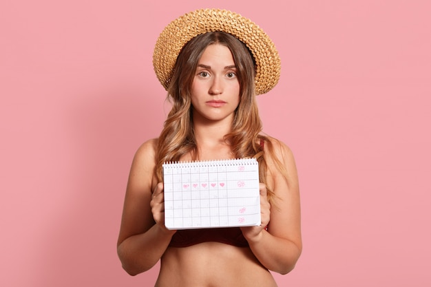 Horizontal shot of beautiful tanned young european female dressed straw hat and swimsuit, holding period calendar, has unhappy expression, has menstuation.
