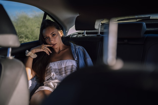 Horizontal shot of a beautiful young caucasian female posing in the back seat of a car in a field