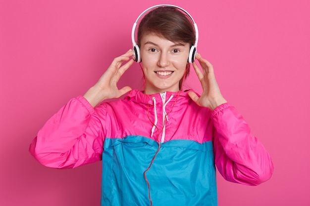 Horizontal shot of beautiful young caucasian girl in sportwear enjoy listening to music with headphones, keeps hands on ears, isoalted over pink wall. fitness, sport and healthy lifestyle concept