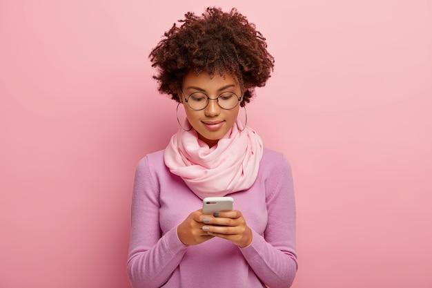 Colpo orizzontale di bella giovane donna con acconciatura afro, utilizza il dispositivo smartphone, concentrato sul display, invia messaggi di testo, connesso a internet wireless indossa sciarpa viola intorno al collo