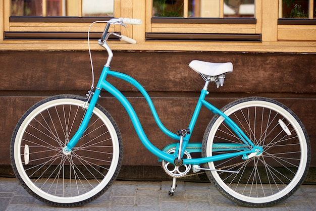 Horizontal shot of a blue city bicycle placed near the wall of a building on the city street