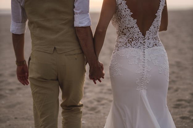 Horizontal shot of a bride and broom holding each other's hands in the beach