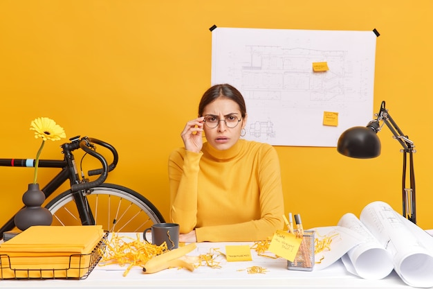 Horizontal shot of brunette woman looks attentively, keeps hand on spectacles tries to see something into distance poses at messy desktop works on drawing for architectural project.