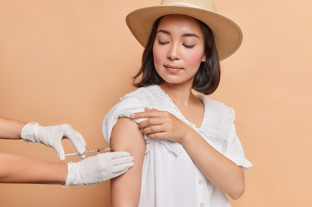 Horizontal shot of brunette young asian woman gets inoculation in shoulder wears fedora and white dress