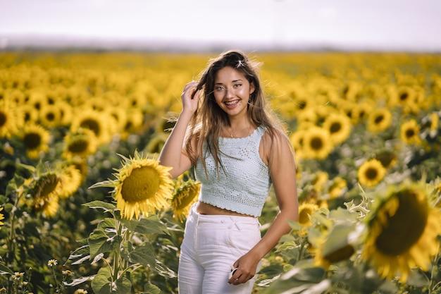 Inquadratura orizzontale di una giovane donna caucasica in posa in un campo luminoso di girasoli in una giornata di sole
