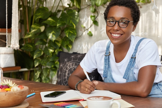 Horizontal shot of cheerful black woman wears spectacles writes list to do in notebook or personal diary