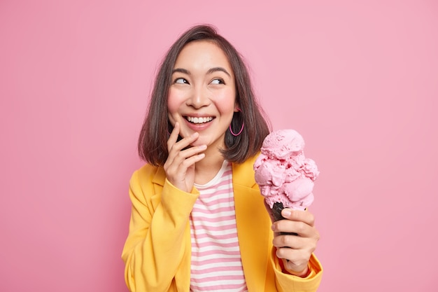 Il colpo orizzontale di allegra giovane donna asiatica bruna distoglie lo sguardo con gioia tiene un delizioso gelato freddo in cialda indossa abiti eleganti e si gode le vacanze estive isolate sul muro rosa.