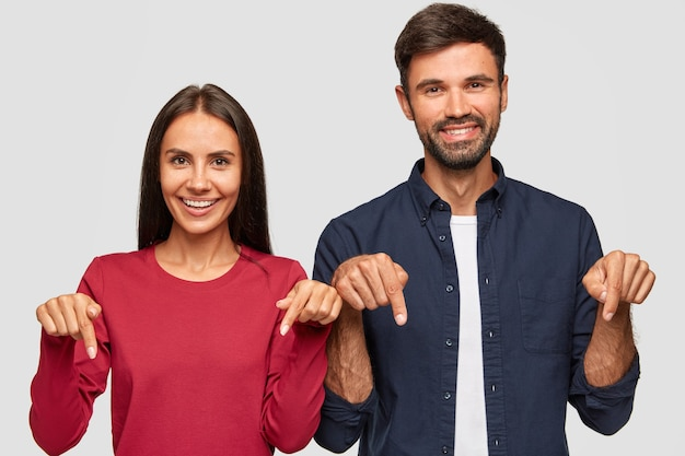 Horizontal shot of cheerful caucasian young adult woman and man point with index fingers down,