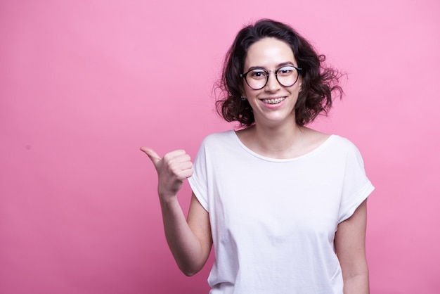 Horizontal shot of cheerful dark haired woman feels overjoyed, dressed casually, demonstrates copy space for your advertisement