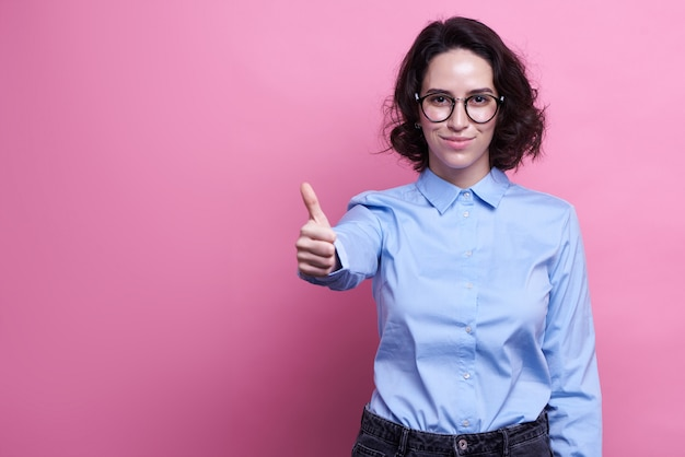Horizontal shot of cheerful dark haired woman feels overjoyed, dressed casually,