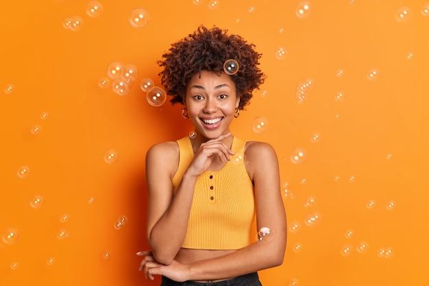 Horizontal shot of cheerful dark skinned woman holds chin