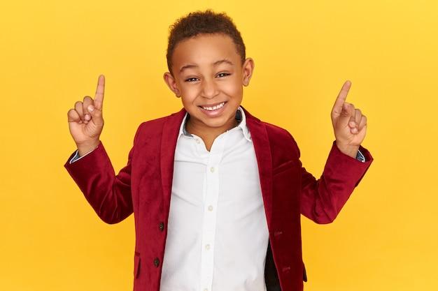 Inquadratura orizzontale di allegro scolaro afroamericano energico sorridente, alzando le dita anteriori, rivolto verso l'alto, indicando la parete in bianco dello studio con lo spazio della copia per il contenuto pubblicitario