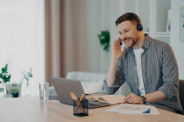 Horizontal shot of cheerful man participates in self improvement webinar wears checkered shirt communicates online by video call uses headset and laptop computer studies online poses at desktop