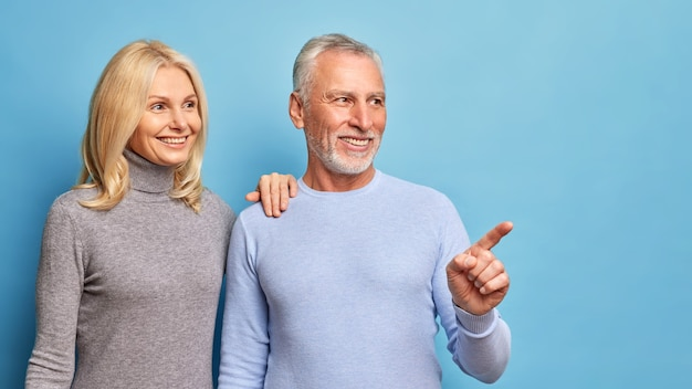 Horizontal shot of cheerful middle aged woman and man smiles gladfully and look into distance.