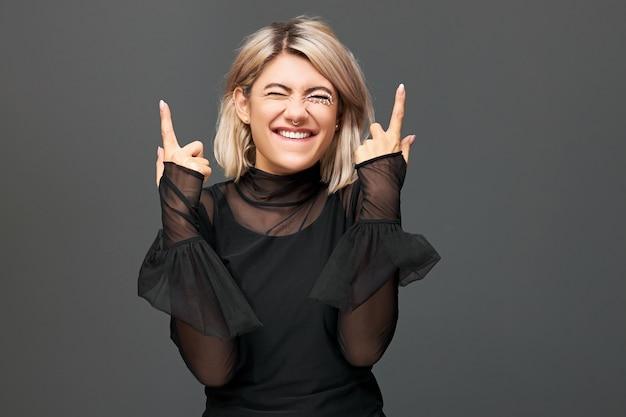 Inquadratura orizzontale di giovane donna europea estatica allegra e felicissima che indossa un abito trasparente elegante che gode di buone notizie positive, esprime gioia, punta il dito indice verso l'alto, celebra il successo
