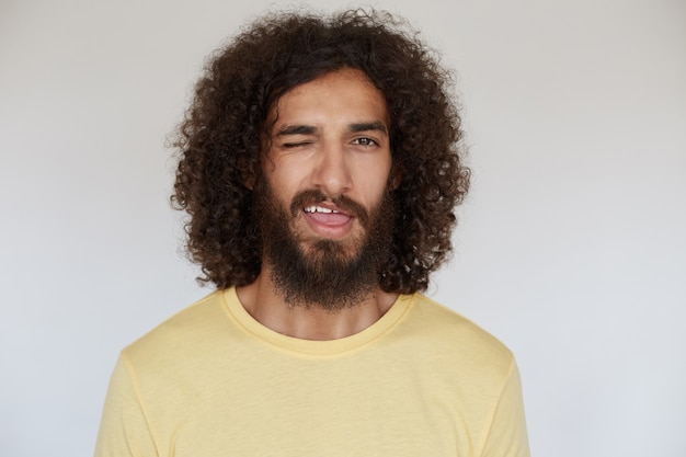 Horizontal shot of cheerful pretty brunette male with curly hair and lush beard giving wink and keeping mouth opened, isolated in yellow t-shirt